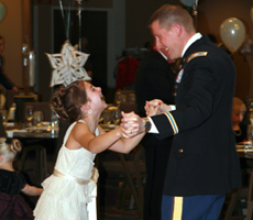 Military father dancing with laughing daughter