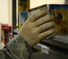 airman selecting a can from food pantry