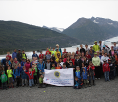 Moms and sons in front of Specer Glacier with banner