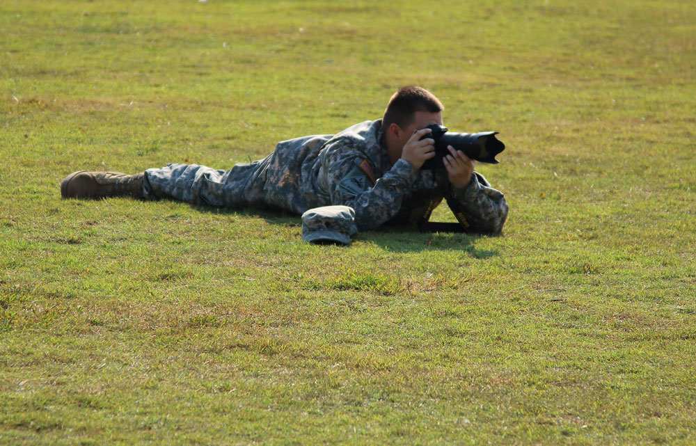Soldier laying on ground taking a photo